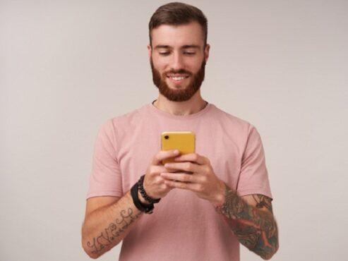 Ilustrasi pria berjenggot bermain ponsel sambil senyum-senyum enggak jelas. (freepik)