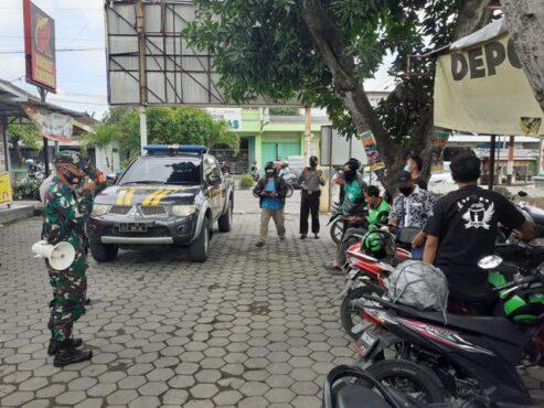 Aparat gabungan menyosialisasikan kebijakan pembatasan sosial kepada driver ojek online di sepanjang Jl. Veteran, Sabtu (9/1/2021). (Solopos-R. Bony Eko Wicaksono)