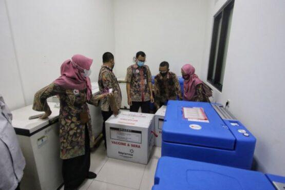 Petugas memeriksa vaksin Covid-19 yang baru tiba di UPT Instalasi Farmasi Dinas Kesehatan Kota (DKK), Solo, Selasa (12/1/2021) petang. (Solopos/Nicolous Irawan)