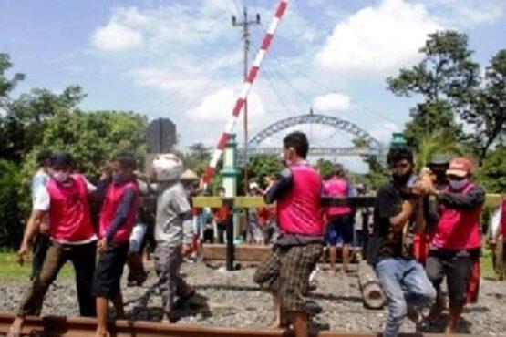 Para warga Siboto beramai-ramai mengangkat portal besi dengan menggunakan bambu dan dipindahkan ke pinggir perlintasan KA di Dukuh Siboto RT 011, Desa Kalimacan, Kalijambe, Sragen, Kamis (18/2/2021). (Solopos.com-Tri Rahayu)