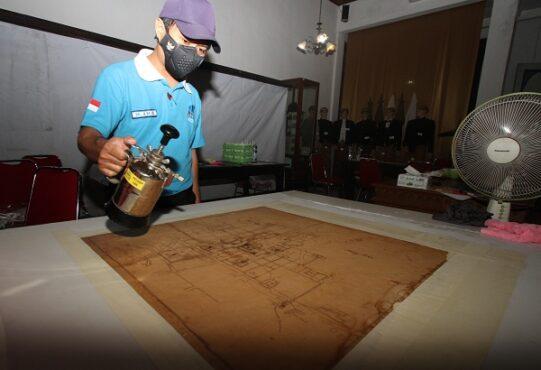 Petugas Arsip Nasional Republik Indonesia (ANRI) merestorasi arsip peta koleksi milik Museum Radya Pustaka, Solo, Rabu (24/2/2021). (Solopos.com/Nicolous Irawan)
