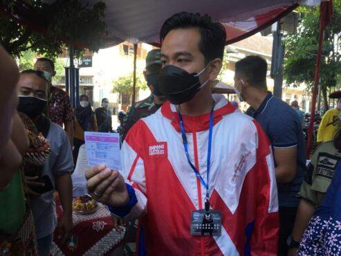 Wali Kota Solo, Gibran Rakabuming Raka, menunjukkan kartu vaksinasi Covid-19, Sabtu (27/2/2021). (Solopos.com/Farida Trisnaningtyas)