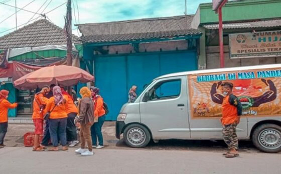 Para sukarelawan SAR Poldes Sragen membagikan nasi bungkus kepada warga di sekitar Pasar Masaran, Sragen, Minggu (28/2/2021). (Istimewa/Poldes Sragen)