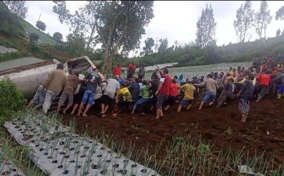 Ratusan warga di sekitar lokasi kejadian berupaya mengevakuasi truk tanki air yang terguling ke area perkebunan di Dukuh Milir, Desa Gumeng, Kecamatan Jenawi pada Minggu (28/2/2021). (Istimewa)