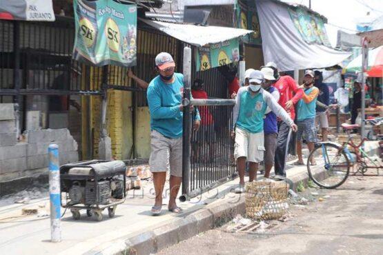 Para pekerja sedang membongkar pagar yang ada di depan Pasar Eks Stasiun Ponorogo, Rabu (3/3/2021). (Istimewa/Pemkab Ponorogo)