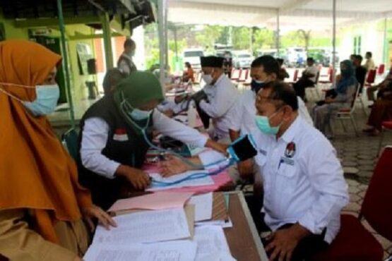 Petugas medis memeriksa tekanan darah Ketua KPU Sragen Minarso sebelum mengikuti vaksinasi di Kantor Kemenag Sragen, Jateng, Senin (1/3/2021). (Solopos.com-Tri Rahayu)