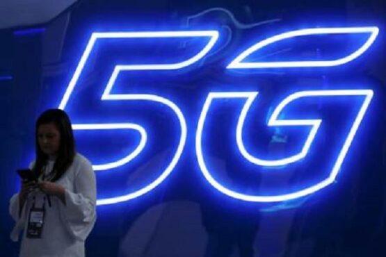 Seorang wanita mengoperasikan ponselnya di dekat logo teknologi 5G. (Bisnis-Reuters-Sergio Perez)