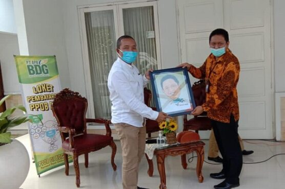 Presdir PT Aksara Dinamika Jogja Arif Budisusilo (kiri) menyerahkan karikatur ke CEO PT WMU Tbk Ali Mas'adi. (Harian Jigja/David Kurniawan)