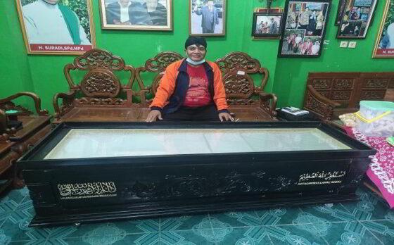Suradi, 63, warga Tandon RT 002/RW 002, Desa Pare, Kecamatan Selogiri, Wonogiri, saat duduk di dekat peti mati yang ia manfaatkan sebagai meja di ruang tamu rumahnya, Rabu (3/3/2021).