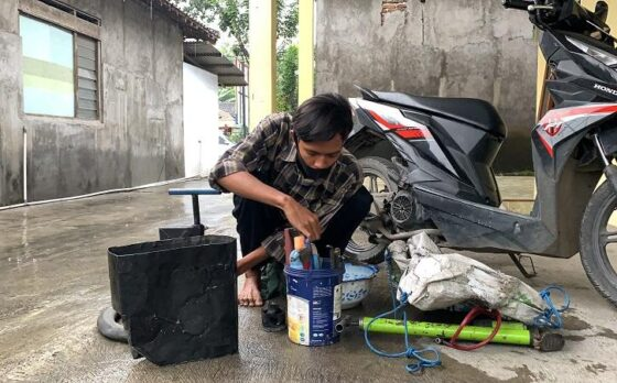 Wahyu Nugroho, 19, sedang menyiapkan alat-alat yang digunakan untuk menambal ban di rumahnya Minggu (7/3/2021). Wahyu yang juga seorang pelajar setiap harinya bekerja sambilan menambal ban sepeda motor panggilan tanpa mematok biaya. (Solopos/Candra Putra Mantovani)