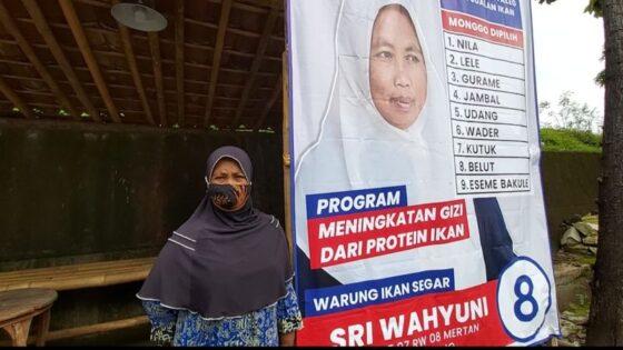 Sri Wahyuni dan baliho yang mendadak menjadi viral gara-gara dibuat layaknya atribut kampanye calon pemilu pada Minggu (7/3/2021). (Solopos/Indah Septiyaning Wardani)