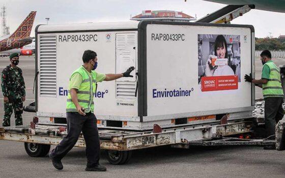 Petugas menurunkan kontainer berisi vaksin Covid-19 saat tiba di Bandara Soekarno-Hatta, Tangerang, Banten, Selasa (12/1/2021). (Antara)