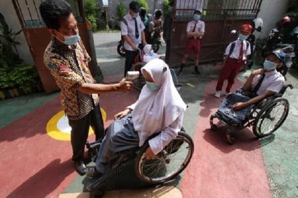 Siswa penyandang disabilitas YPAC, Solo, menggunakan kursi roda antre dicek suhu tubuhnya saat akan mengikuti simulasi pembelajaran tatap muka (PTM) di sekolah, Selasa (6/4/2021). (Solopos.com-Nicolous Irawan)