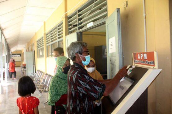 Seorang petugas menunjukkan cara menggunakan antrean pasien mandiri (APM) di depan pintu pelayanan kesehatan darurat Puskesmas Karangmalang, Sragen, yang bertempat di Gedung SMA PGRI Sragen, Selasa (13/4/2021).(Espos/Tri Rahayu)