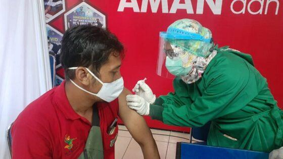 Seorang petugas menyuntikkan cairan vaksin Covid-19 di lengan seorang pedagang pasar tradisional di Kota Madiun, Jumat (16/4/2021). (Abdul Jalil/Madiunpos.com)
