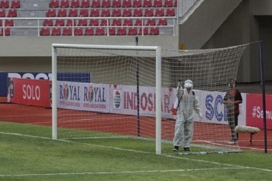 Petugas menyemprotkan cairan disinfektan ke jarring di salah satu gawang di lapangan Stadion Manahan, Solo, sebelum pertandingan Piala Menpora 2021, Minggu (21/3/2021). (Solopos.com/Nicolous Irawan)