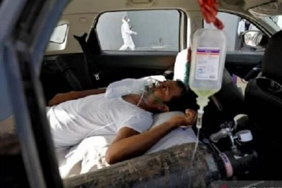 Seorang pasien dengan gangguan pernapasan berbaring di dalam mobil sambil menunggu masuk rumah sakit Covid-19 untuk perawatan, di tengah penyebaran Covid-19 di Ahmedabad, India, Kamis (22/4/2021). (Antara-Reuters)