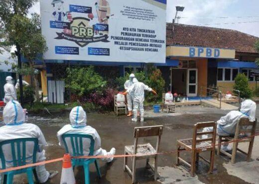 Sukarelawan di Klaten disemprot disinfektan seusai memakamkan jenazah dengan prosedur Covid-19. (Istimewa/Dokumentasi Solopos)
