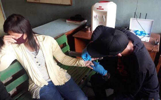 Leni Susanti, 32, menyembunyikan wajahnya seraya menahan takut saat petugas Satpol PP dan Damkar Sragen berusaha melepas cincin kawin, Minggu (11/4/2021). (Solopos.com/Moh. Khodiq Duhri)