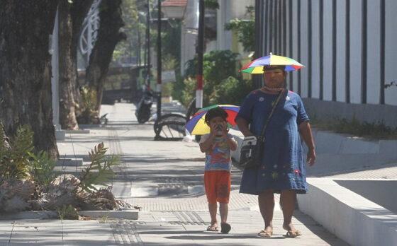 Anak-anak bersama orang tuanya memakai topi payung untuk melindungi diri dari sengatan matahari saat berjalan melintasi jalur pedestrian di Jl. Ir. H. Juanda, Pucangsawit, Jebres, Solo, Kamis (22/4/2021). (Solopos/Nicolous Irawan)