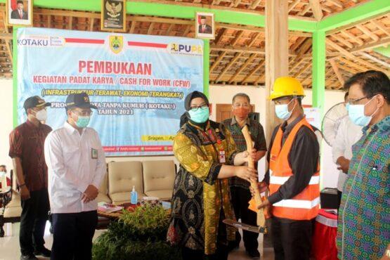 Bupati Sragen Kusdinar Untung Yuni Sukowati menyerahkan cangkul dan perlengkapan kerja kepada perwakilan MBR yang ikut serta dalam Program PKT di Balai Desa Bandung, Ngrampal, Sragen, Selasa (20/4/2021).(Espos/Tri Rahayu)