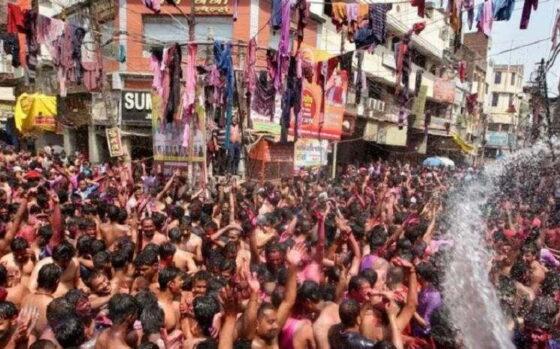 Para pria bersorak saat mereka disiram air selama perayaan Holi, di tengah penyebaran Covid-19 di Prayagraj, India, Senin (29/3/2021). (Antara/Reuters)