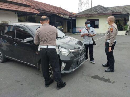 Kasatlantas Polresta Kompol Adhytiawarman Gautama Putra (kanan) memeriksa mobil yang diduga menggunakan pelat nomor palsu dan terdeteksi sistem ETLE di Mako Satlantas Polresta Solo, Rabu (7/4/2021) sore. (Istimewa/Humas Satlantas Polresta Solo)