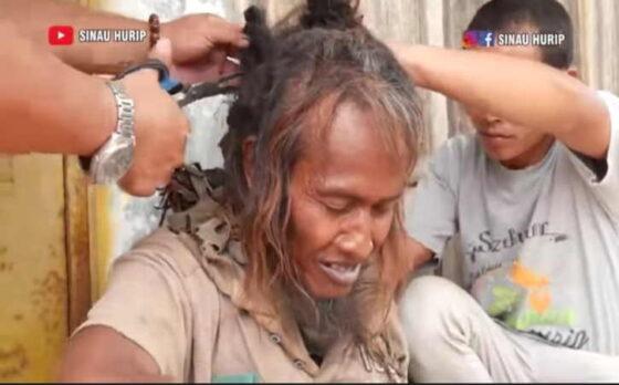 Tim Sinau Hurip berusaha membersihkan kuku dan memotong rambut gimbal Mbah Pang, ODGJ penunggu Pasar Tunggul, Gondang, Sragen, belum lama ini. (Istimewa/Youtube Sinau Hurip)