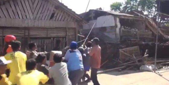 Warga bergotong royong merobohkan rumah warga korban gempa. (okezone.com)