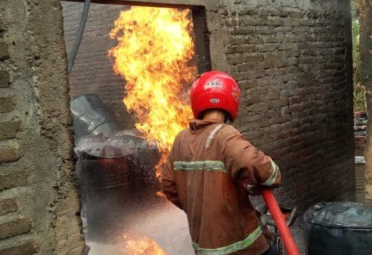 Seorang petugas pemadam kabakaran Satpol PP Sragen memadamkan api di gudang penyimpanan BBM di rumah milik warga di Dukuh Pilangsari RT 031, Desa Ketro, Tanon, Sragen, Sabtu (8/5/2021). (Solopos.com-Satpol PP Sragen)
