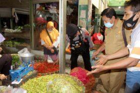 Seorang pedagang cabai, Yuliatman (kanan), mempersilakan petugas untuk memeriksa kondisi cabai yang dipasarkan di los miliknya di Pasar Bunder Sragen, Senin (10/5/2021). (Solopos/Tri Rahayu)