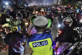Polisi menghalau pemudik bersepeda motor yang melawan arah untuk menghindari posko penyekatan mudik di Kedungwaringin, Kabupaten Bekasi, Jawa Barat, Minggu (9/5/2021). (Antara/Fakhri Hermansyah)