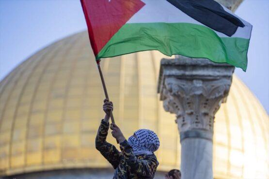 Pengunjuk rasa mengibarkan bendera Palestina dalam aksi demo setelah pelaksanaan Salat Idulfitri di kompleks Masjidil Aqsa di Jerusalem, Kamis (13/5/2021). (Anadolu Agency/Mostafa Alkharouf)