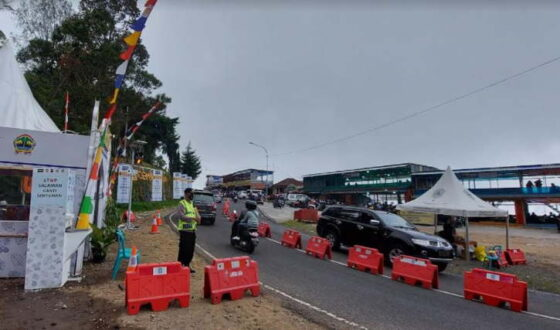 Anggota Polres Karanganyar berada di depan pos penyekatan kendaraan di wilayah perbatasan Jawa Tengah dan Jawa Timur, tepatnya di Cemara Kandang pada Minggu (16/5/2021). (Solopos.com/Sri Sumi Handayani)