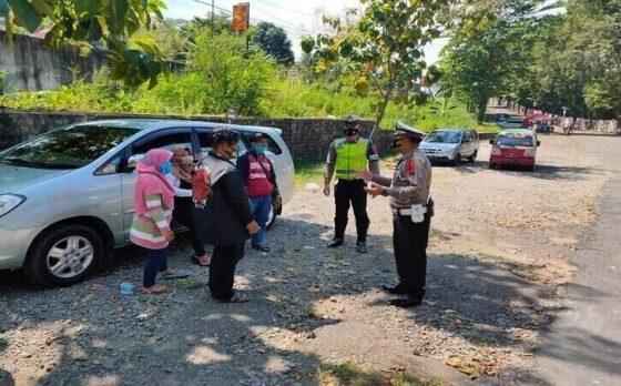 Polisi memberi informasi kepada warga bahwa Wisata Waduk Gajah Mungkur atau WGM Wonogiri tutup. Mereka diminta selalu memakai masker. Foto diambil di depan gerbang Wisata WGM, Jumat (14/5/2021). (Solopos/Rudi Hartono)
