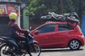 Brak! Eh Motornya Nangkring di Atap Mobil Seusai Tabrakan