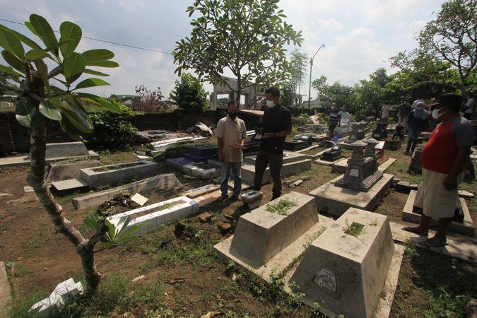 Warga mendata makam yang dirusak di kompleks permakaman umum Cemoro Kembar, Mojo, Pasar Kliwon, Solo, Senin (21/6/2021). (Solopos/Nicolous Irawan)