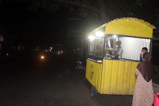 Seorang pedagang roti bakar melayani pembeli di pinggir Jl Raya Sukowati Sragen saat diberlakukan pemadaman lampu jalan selama dua jam, Senin (12/7/2021) malam. (Solopos/Tri Rahayu)