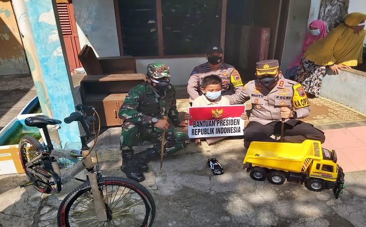 Azhar Al Ghifari Putra Setiawan, 8, asal Sukoharjo, Jawa Tengah menerima bantuan dari Presiden Joko Widodo pada Jumat (30/7/2021). (Solopos.com/ Indah Septiyaning Wardani)