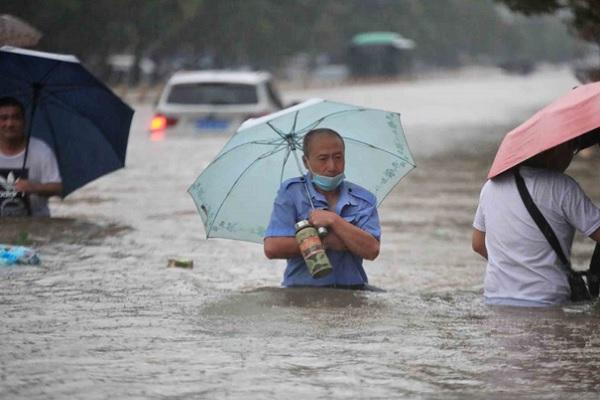 Warga berjalan menerobos banjir yang merendam jalan di tengah masih turunnya hujan di Zhengzhou, Provinsi Henan, Selasa (20/7/2021). (Antara-China Daily via Reuters)