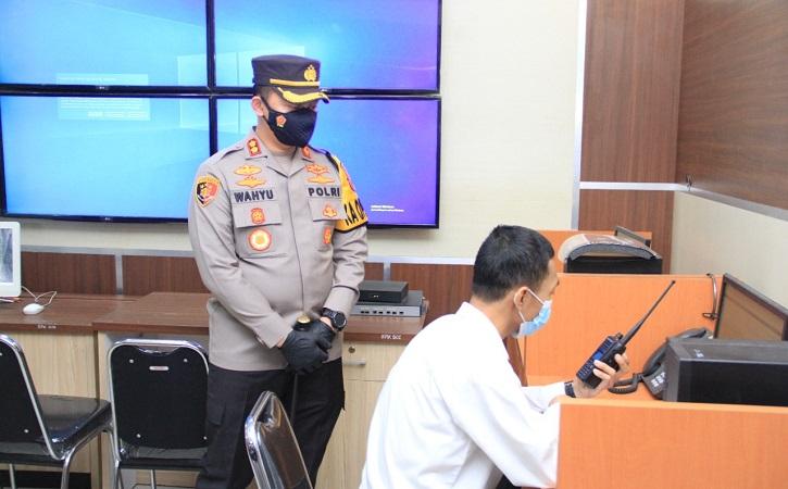 Kapolres Sukoharjo AKBP Wahyu Nugroho Setyawan saat melihat proses Damar Primas Suganda mengoperatori layanan call center hotline 110 Polres Sukoharjo pada Kamis (29/7/2021). (Solopos.com/Indah Septiyaning Wardani)