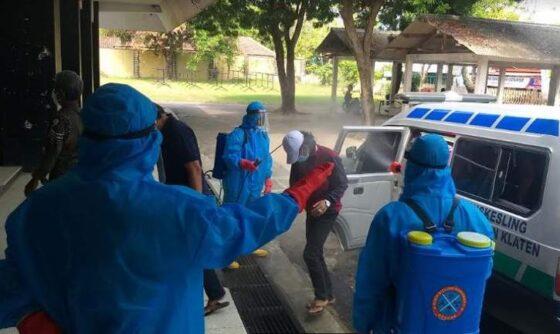 Petugas menyemprot  cairan desinfektan ke warga yang akan menjalani isolasi di GOR Gelarsena Klaten, Jumat (23/7/2021). (Solopos.com/Ponco Suseno)