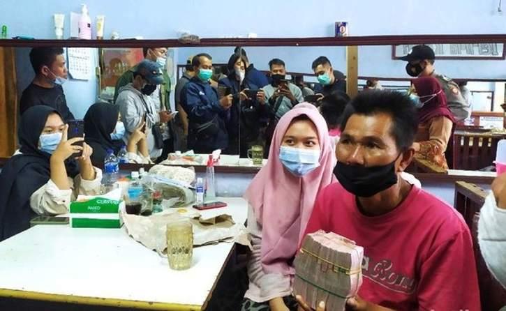 Mang Eman, pedagang agar-agar, menunjukkan uang hasil donasi senilai Rp108 juta. (detik.com)