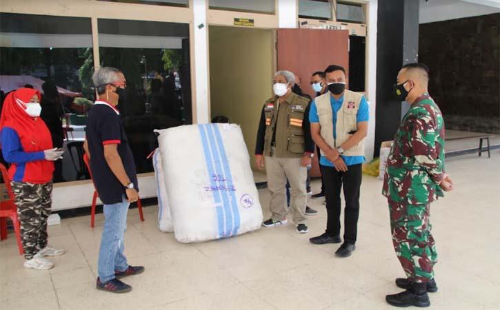 Bambang Supriyambodo, 61, penyintas Covid-19 menyerahkan bantuan APD di GOR Gelarsena Klaten, Minggu (25/7/2021). (Solopos-Taufiq Sidik Prakoso)