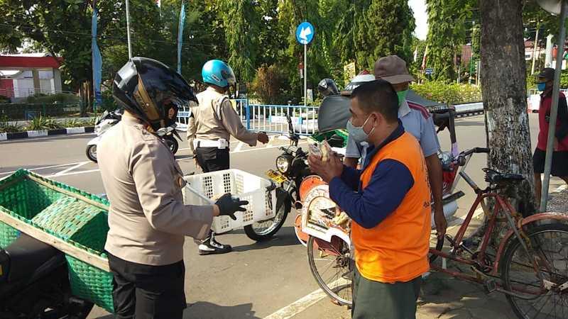 Polisi menggunakan sepeda motor berberonjong membagikan bansos paket sembako di gang-gang sempit, Minggu (25/7/2021). (Istimewa/Polsek Sukoharjo Kota)