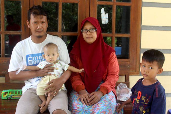 Pasangan Joko Triyanto dan Ermawati memangku anak bungsu mereka, Azalea, di rumahnya, Dukuh/Desa Taraman, RT 002/RW 001, Sidoharjo, Sragen, Minggu (1/8/2021). (Solopos/Tri Rahayu)