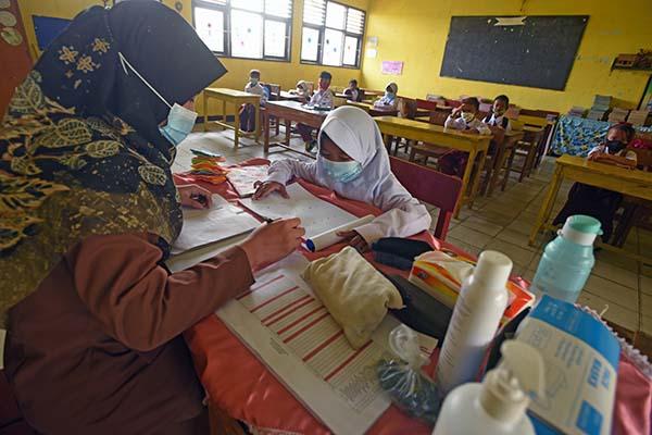 Guru membimbing siswa saat mengikuti proses belajar mengajar tatap muka terbatas di SD Negeri Pejaten I di Kramatwatu, Serang, Banten, Senin (23/8/2021). Pemerintah setempat secara selektif memberi izin bagi sekolah-sekolah di zona hijau memberlakukan pembelajaran tatap muka dengan pembatasan separuh dari kapasitas kelas serta penerapan protokol kesehatan. ANTARA FOTO/Asep Fathulrahman/wsj.