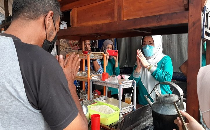 Bupati Sukoharjo Etik Suryani berdialog dengan pasangan suami istri Cahyo Yulianto, 50 dan Wiwin Haryati, 48 di lapak wedangan di depan SMP Negeri 3 Kartasura, Jumat (17/9/2021). (Solopos.com/Indah Septiyaning Wardani)