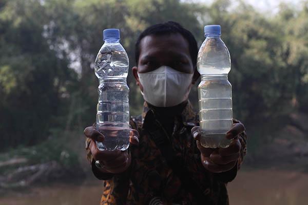 Petugas Perumda Air Minum Toya Wening Solo menunjukkan sampel air baku yang sudah tercemar limbah alkohol dan yang belum tercemar di bantaran Sungai Bengawan Solo, Nusupan, Kadokan, Grogol, Sukoharjo, Selasa (7/9/2021). Air baku tercemar limbah alkohol tersebut merupakan permasalahan tahunan saat memasuki puncak musim kemarau sejak 2018 hingga saat ini belum ada solusi. (Solopos/Nicolous Irawan)