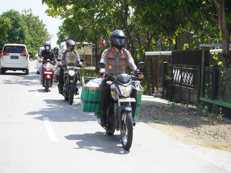 Kapolres Sukoharjo, AKBP Wahyu Nugroho Setiawan SIK mengendarai sepeda motor berberonjong yang berisi paket sembako, Sabtu (4/9/2021).
